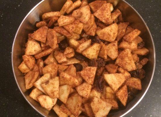 Schil de appels, snij ze in partjes en snij ze daarna in plakjes. Voeg de goed uitgeknepen rozijnen toe en mix dit alles met het zakje kaneelsuiker.